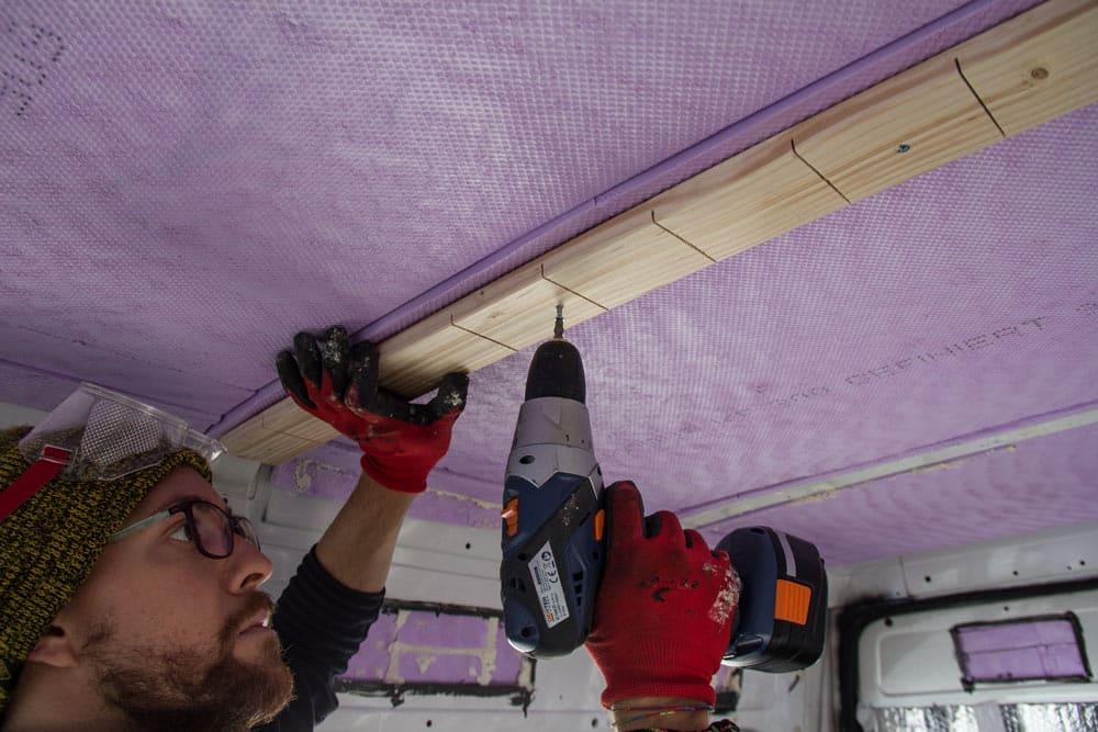 Valerio mentre fissa il supporto di legno sul montante del tetto